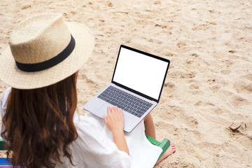 Mockup image of a woman using and typing on laptop computer with blank desktop screen while sitting on a beach chair