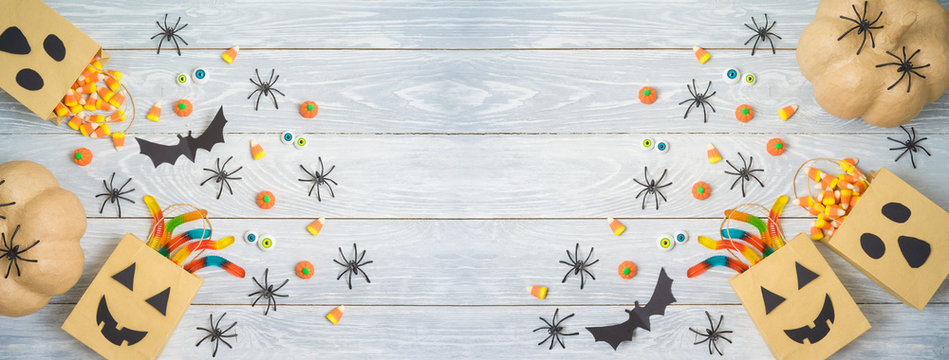 Halloween holiday party background with gift paper bags and candy .Top view from above. Flat lay
