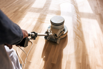 a professional master cleans the floor with a polishing machine