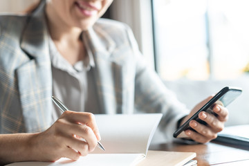 Young contemporary businesswoman with pen and phone writing down working plan