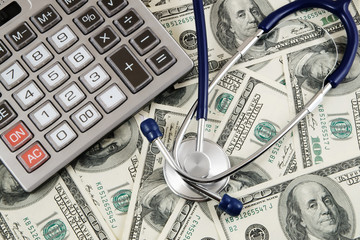 Calculator and stethoscope on banknotes background, cost of healthcare concept