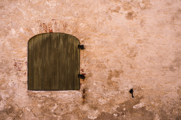 old arched Window closed by wooden shutters and red wall