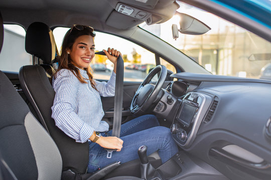 Young girl is fastening her seat belt. Photo of a business woman sitting in a car putting on her seat belt.  Woman fastening seat belt in the car, safety concept