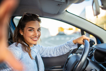 Smiling young woman taking selfie picture with camera in car. Holidays and tourism concept - smiling teenage girl taking selfie picture in car. Beautiful young woman in car, taking selfie