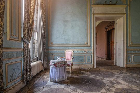 Chaise rose avec une table dans un vieux château style baroque
