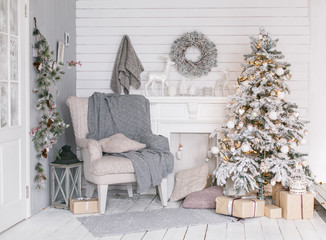 Stylish Christmas interior with a soft gray armchair. Comfort home. Christmas tree with presents...