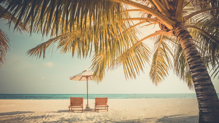 Fototapete - Beautiful tropical sunset scenery, two sun beds, loungers, umbrella under palm tree. White sand, sea view with horizon, colorful twilight sky, calmness and relaxation. Inspirational beach resort hotel