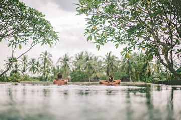 Fotorolgordijn Khaki Infinity pool with a view on palm trees, Ubud, Bali