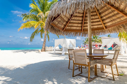 Cafe on the beach, ocean and sky, tropical resort or hotel background concept. Summer vacation or holiday, family travel