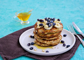Banana oat pancakes with hazelnuts, sliced banana, honey and honeysuckle on a white plate on a turquoise concrete background. American food. Baking with oatmeal.