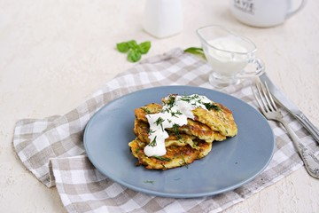Fritters zucchini with feta cheese on a gray plate on a light concrete background. Served with sour cream. Zucchini recipes. Selective focus.