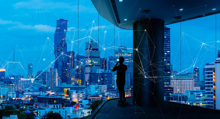 Wall Mural - Businessman standing using smart phone in modern space watching city night view.Business with ambition and vision concept.and wireless network low poly line.