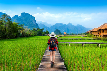 Canvas Print - Tourism with backpack walking on wooden path, Vang vieng in Laos.