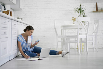 Busy woman making notes while working at home stock photo