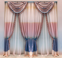 Modern beige cotton curtains with wide blue and pink stripes decorated with classic pelmet