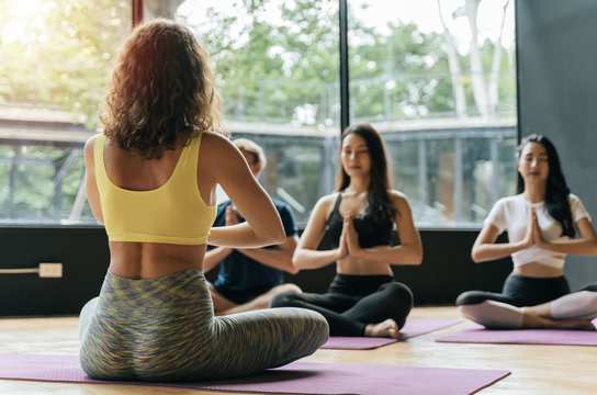 group of athletic young diverse cultures sporty people practicing yoga lesson with instructor in class at fitness gym, bodybuilder, healthy lifestyle, fitness, workout and sport training concept