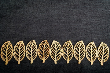 Line with nine delicate light brown wooden leaves on dark grey textile material background, top view with space for text on the right side, flat lay with laser cut wooden objects Wall mural