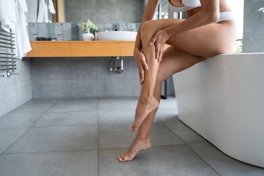 Caucasian woman rubbing an emollient cream into the skin