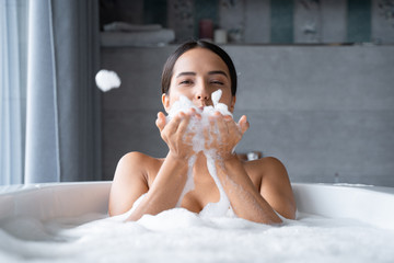 Relaxed young woman taking a bath with foam
