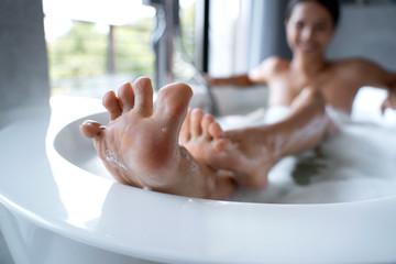 Well-groomed feet of a female taking a bath