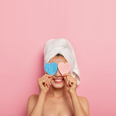 Photo of cheerful healthy European woman keeps two sponges on eyes, hides face and smiles happily, takes bath, has naked body, models over pink background, copy space for your advertising content