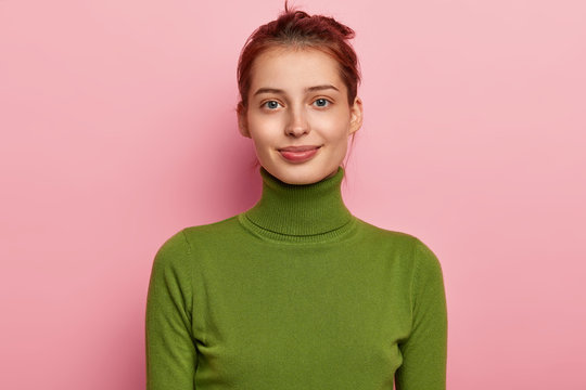 Portrait of beautiful young lady has dark combed hair, appealing appearance, wears casual green turtleneck, looks gladfully into camera, poses against pink background, feels pleased to have day off
