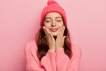 Portrait of pleased European woman touches both cheeks with palms, wears knitted hat and sweater, closes eyes with satisfaction, imagines future date with boyfriend enjoys winter time isolated on pink
