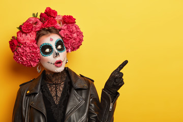 Terrified woman wears professional makeup for horror, dressed in black clothes, points away, wears gloves, red peonies wreath, celebrates Halloween holiday or Day of Death. Image of Calavera Catrina