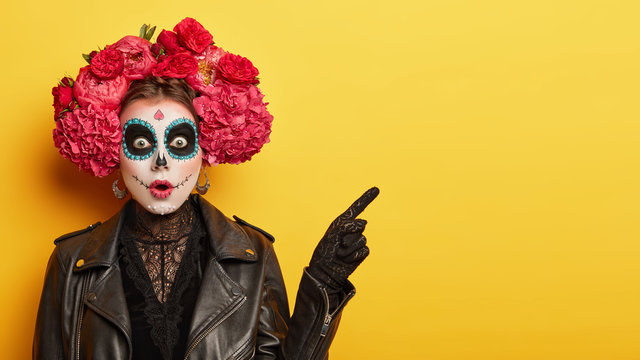 Happy Halloween concept. Scared horrible female in special outfit, wears white clay skull, professional makeup to look spooky, wears black clothes points away on blank space against yellow background
