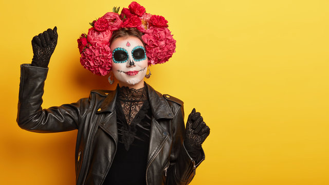 Pleased female has mysterious image, wears black lace dress and gloves, dances during halloween party, has professional painted face resembles skulls, has flower wreath on head. Mexican Day of Death