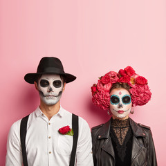 Lovely couple wear zombie costume for Halloween, have skull makeup, man wears hat and white shirt with red rose in pocket, woman in black leather jacket and flower wreath, wait for party together