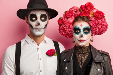 Halloween face art. Woman and man stand together in mexican outfit, spend time in cemetery, remember dead people during day of death, visit zombie party, express horror. Typical holiday in Mexico