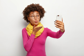Portrait of cute African American woman sends air kiss, takes selfie via smartphone, wears transparent glasses, makes rounded lips, wears vivid clothes, isolated over white wall. Time for making pics
