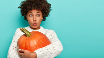 Headshot of dark skinned curly woman keeps lips rounded, holds ripe pumpkin, picks up autumn harvest, prepares for special holiday, wears white winter sweater, isolated over blue background.