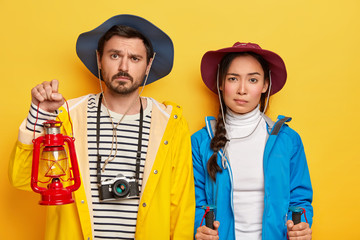 Indoor shot of unhappy mixed race woman and man stand next to each other, use kerosene lamp for lightening, trekking poles, professional camera to make photos during camping trip, isolated on yellow
