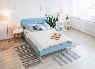 Scandinavian interior design. White and blue pillows on the king size bed with knit blanket in the minimal bedroom interior with plants, frame poster mock up and shelves. Coffee cup and tray. Top view