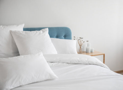 White pillows and duvet on the blue bed. White pillows, duvet and duvet case on a blue bed. White bed linen on a blue sofa. Bedroom with bed and bedding. Front view