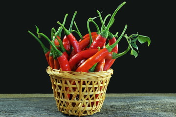 Canvas Prints Hot chili peppers ripe red hot chili pepper isolated in basket on black background