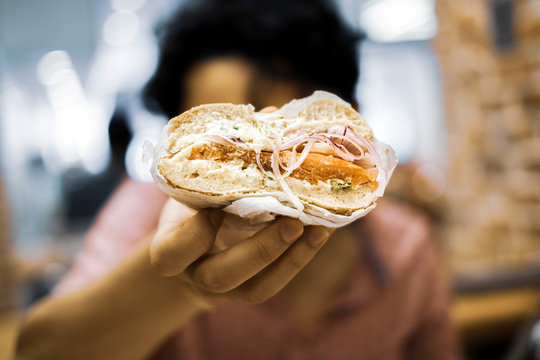 Person holding half a lox bagel