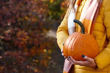Woman holding orange pumpkin, fall concept