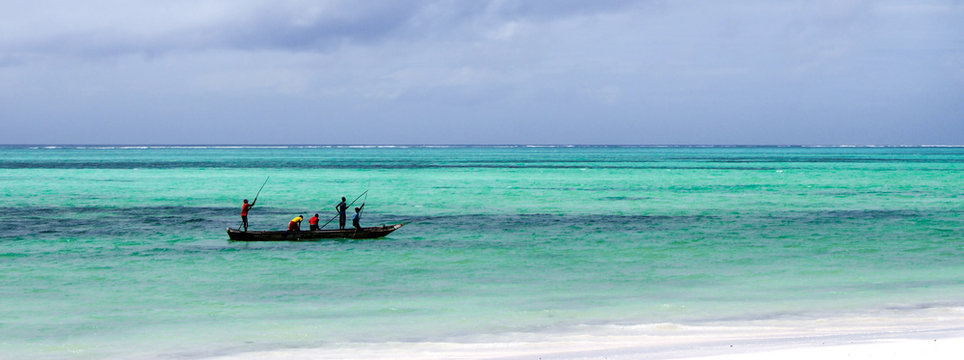 Unidentified fishermen paddling their boat along a shallow coral reef