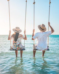 Couple enjoying a swing at Holbox Island in the Caribbean Ocean of Mexico