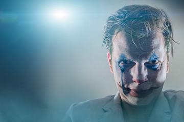 Halloween theme. The crazy joker face. Man in mime makeup cosplay