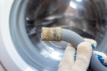 Hand of a plumber holding a broken flexible drain hose of washing machine, clogged and covered with lime scale, dirt limescale and rust
