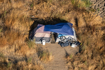 Homeless people live in tents in city outskirts in many areas of California, including in the Napa Valley.
