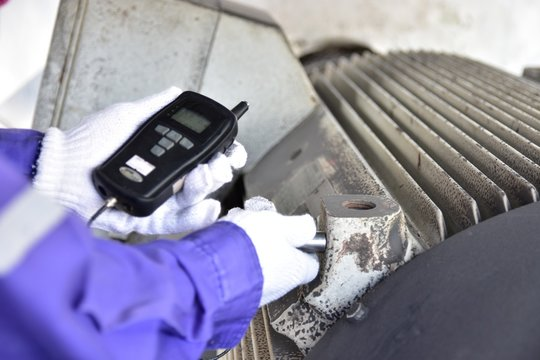 Inspector using a Handheld Vibration Tester  for checking bearings and overall vibration of motor. Selective focus on inspection area.