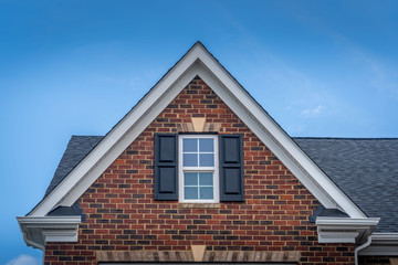 Fototapeta Gable with red brick facade siding, double hung window with white frame, vinyl shutters on a pitched roof attic at a luxury American single family home neighborhood USA obraz