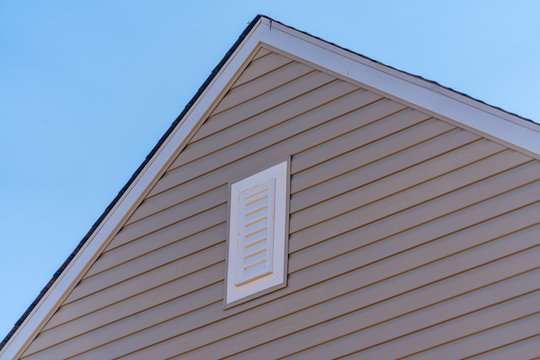 Gable with beige horizontal vinyl lap siding,  classic vertical surface mount PVC gable vent  on a pitched roof attic at an American single family home neighborhood USA