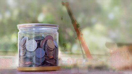 Business concept:  many coins in the glass with blurred picture of construction background.