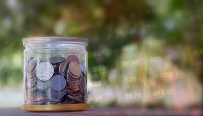 Business concept:  many coins in the glass with blurred picture of stock graph background.